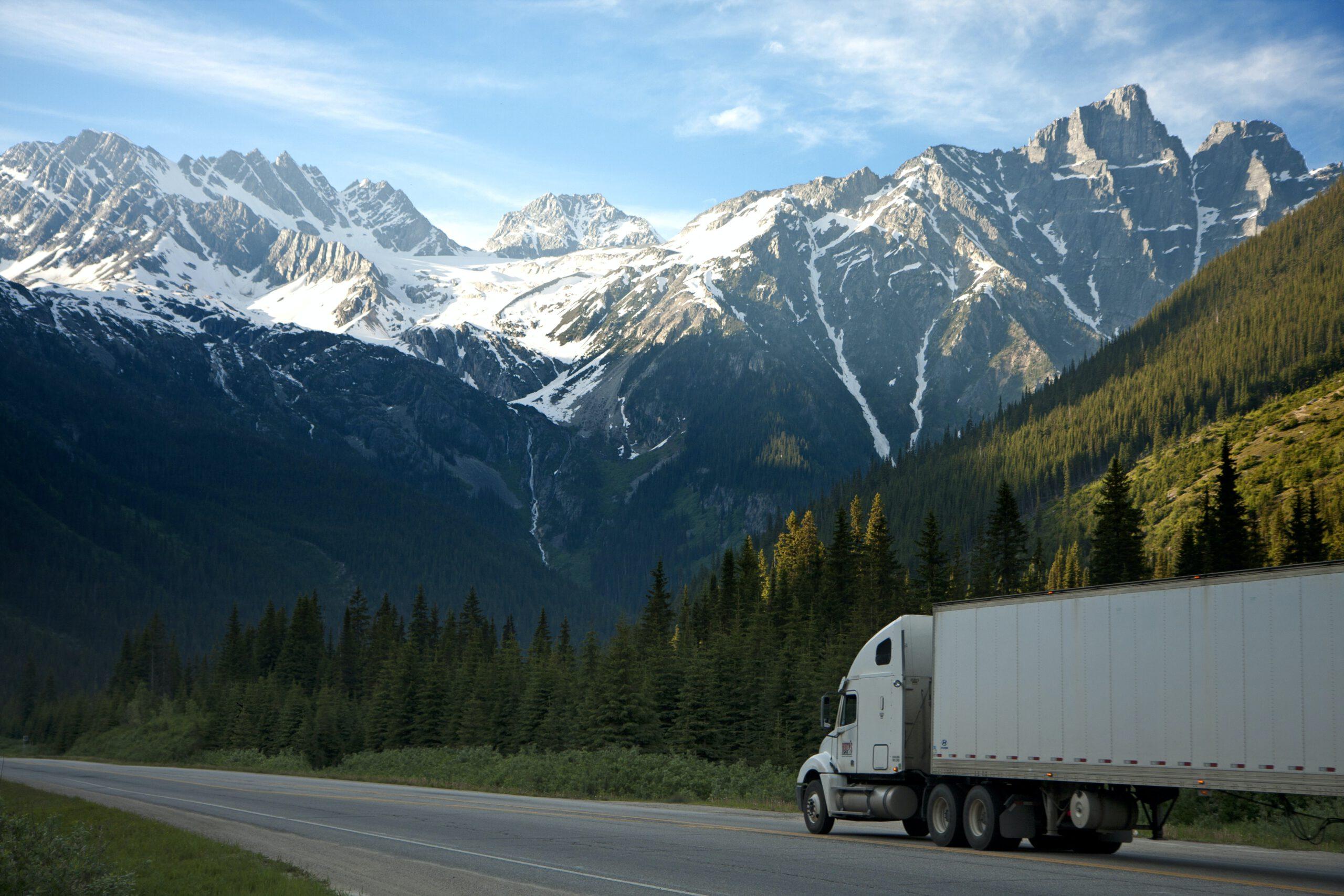 white-dump-truck-near-pine-tress-during-daytime-93398